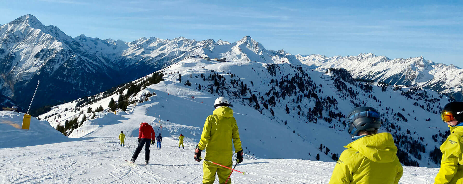 Mehrere Skifahre fahren gemütlich entlang, im Hintergrund eine Bergkulisse